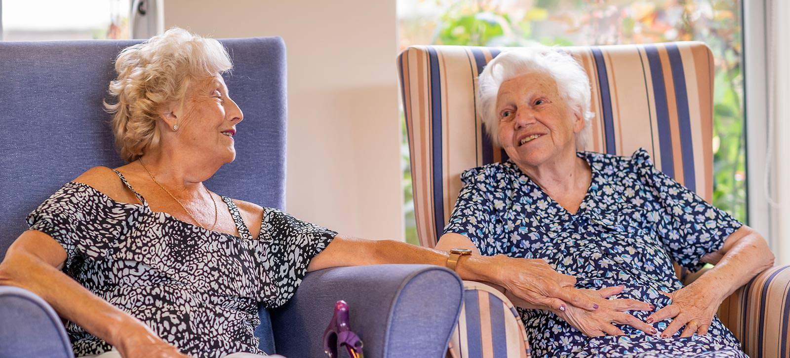 Two ladies chatting in armchairs