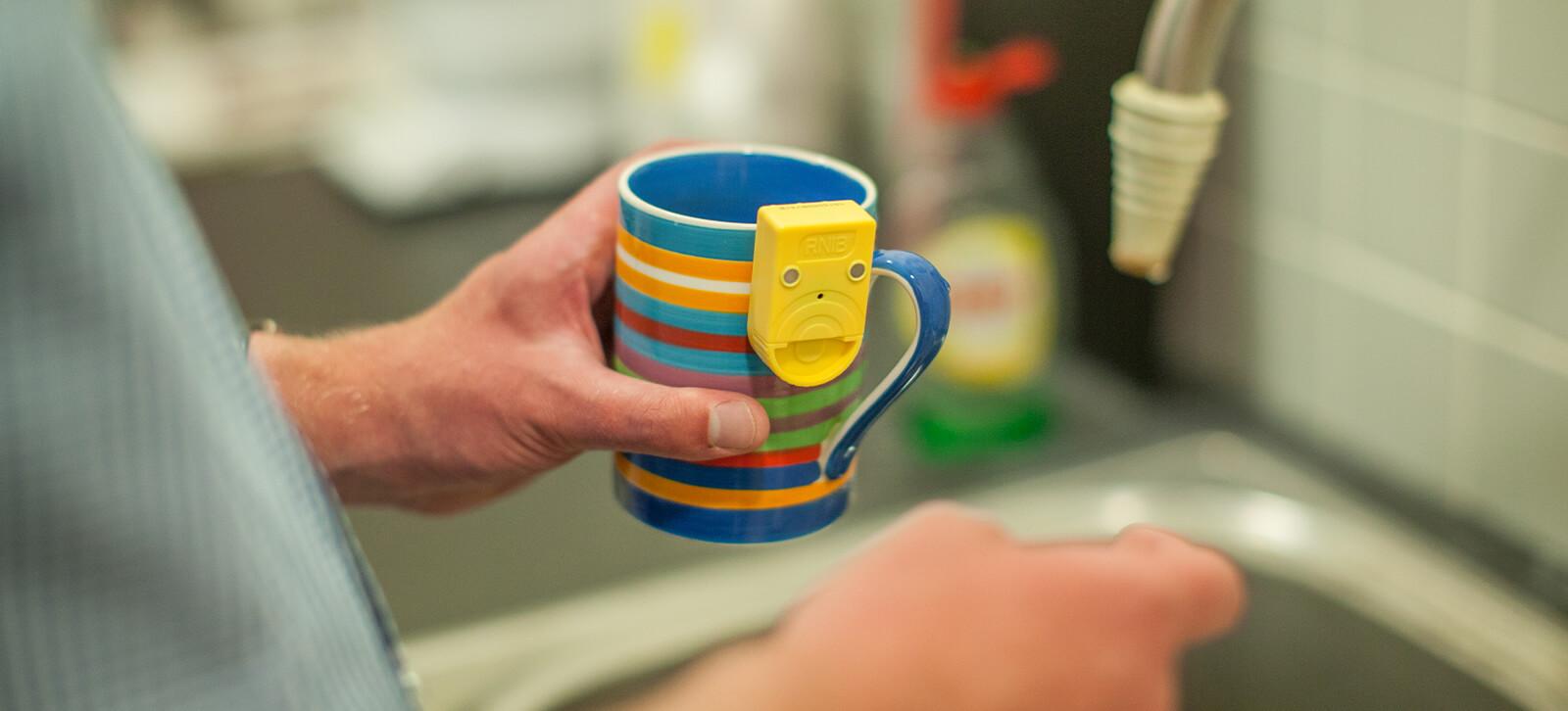Someone holding a mug with a sensor on the side