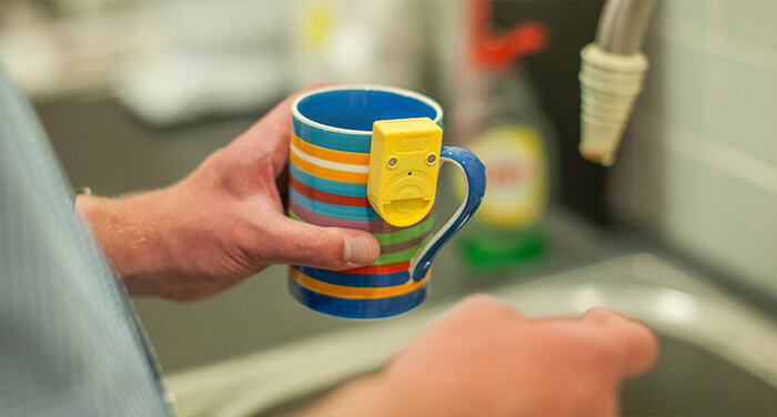 Someone holding a mug with a sensor attached to the side