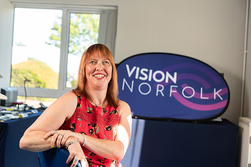 Penny in front of Vision Norfolk Logo